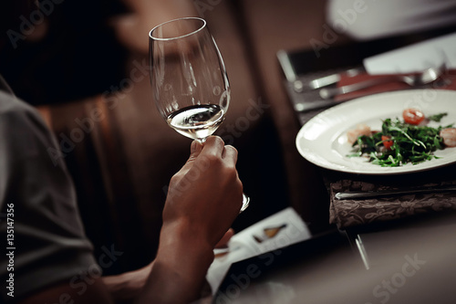 Man with glass of wine in one hand and menu Poster