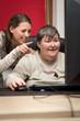 Pflegerin und geistig behinderte Frau am Computer, Bildung und T