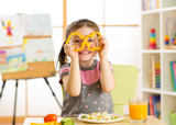 Child girl having fun with food vegetables at nursery room