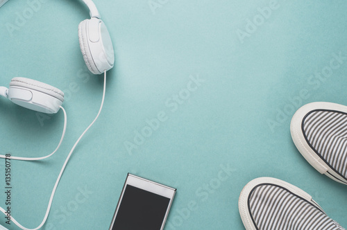 Shoes and gadgets on a bright green background