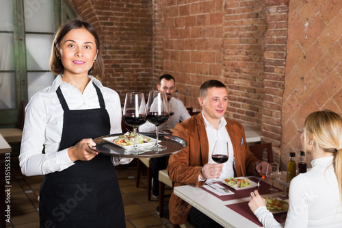 attractive woman waiter demonstrating restaurant to visitors