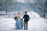 Bride and groom among snowy landscape.