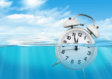 Alarm clock in water, waste of time concept