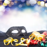 Black mask with masquerade decorations border on blue bokeh background with copy space
