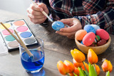 Woman painting Easter eggs on wooden table