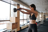 Fitness woman doing exercices with kettleball in gym