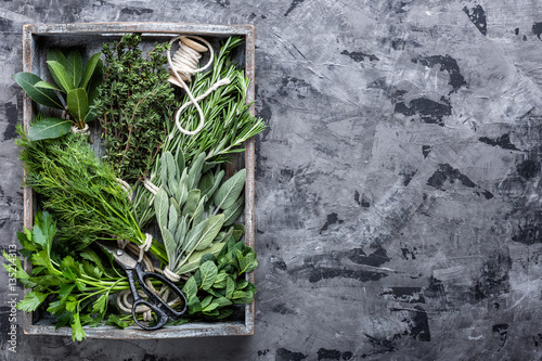 fresh herbs in wooden box on stone background with space for text
