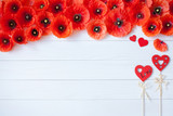 Wooden background with red flowers poppies and hearts