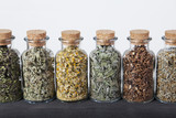 Different kinds of herbs for tea inside glass bottles.