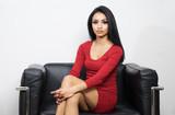 Beautiful woman wearing red dress sitting on black chair