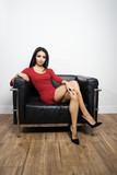 Beautiful woman in red dress sitting on black chair