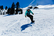 Young mixed race woman wearing teal jacket and white helmet snowboards on a clear blue day