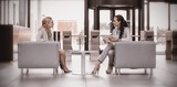 Businesswomen sitting in armchair and having conversation