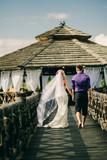 bride and groom walk on beach resort