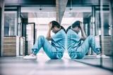 Stressed nurse sitting on floor