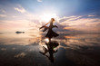 Elegant woman dancing on water. Sunset and silhouette.