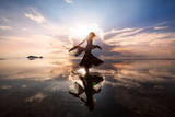 Fototapety Elegant woman dancing on water. Sunset and silhouette.