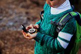 little boy travels with compass in green forest