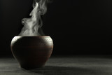 A bowl of hot food and steam on dark background.