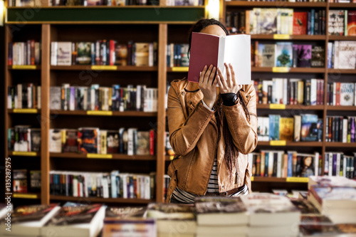 Woman Reading at a Bookstore Poster