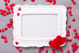 Empty frame and many  decorative red hearts on textured grey bac