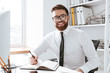 Cheerful businessman sitting in office while writing notes