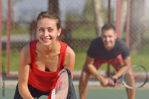 Valokuva Couple playing doubles at the tennis court