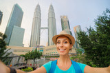 Travel and technology. Young smiling woman taking selfie while walking near Petronas Twins Towers in Kuala-Lumpur, Malaysia, 23 November 2015.