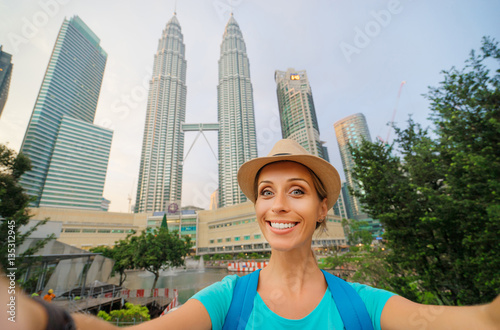 Aluminium Kuala Lumpur Travel and technology. Young smiling woman taking selfie while walking near Petronas Twins Towers in Kuala-Lumpur, Malaysia, 23 November 2015.