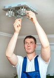 Male electrician changing lamp bulb.