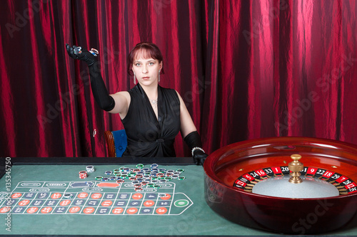 young woman wearing  black gloves and black dress plays in a casino Obraz na płótnie