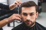 Skillful hairdresser cutting male hair