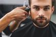 Confident guy sitting at beauty salon