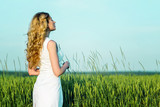 Girl in a wheat field. Springtime green field growing harvest