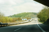 Sunny day over German highway - Bundesautobahn or Federal Motorway highway with busy traffic on a spring day with beautiful green fields and blue clouds