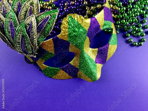 Mardi Gras mask and beads on a purple background  - 135370119
