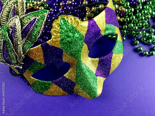Mardi Gras mask and beads on a purple background  - 135370125