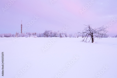 Fotobehang Purper Sunrise over a cold winter landscape with beautiful illuminated clouds