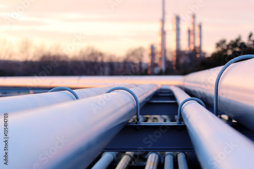 steel long pipes in crude oil factory during sunset Poster
