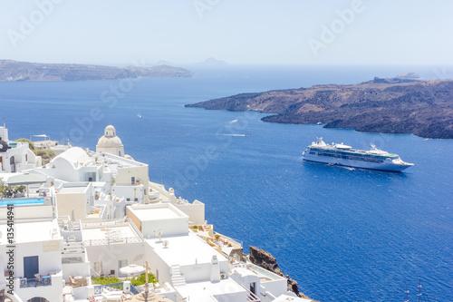 Beautiful panoramic view on the mediterranean sea, caldera and volcano. Traditional white architecture of Santorini island, Thira, Greece. Cruise ship in blue sea.