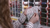 Female seamstress with wavy hair selects the thread of white lace. Woman stands in front of racks with colored spools strands, which applies the material with patterns in the form of flowers for a