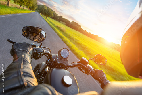 Driver riding motorcycle on an asphalt road Poster