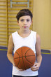 teen boy with basketball ball in gym