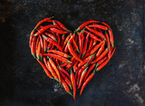 Red chili peppers in heart shape, for valentine's day on old black metal background.