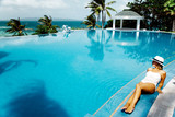 Woman resting in infinity pool with ocean view - 135427116