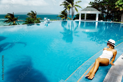 Woman resting in infinity pool with ocean view