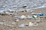 Fototapety Beach pollution. Plastic bottles and other trash on sea beach