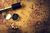 vintage compass and spyglass on old world map. copy space