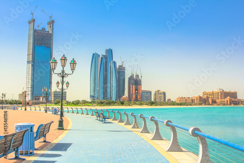 Poster Abu Dhabi Dhabi skyline from cycle paths of Corniche. Abu Dhabi, United Arab Emirates, Middle East. Modern skyscrapers and landmark on background. Summer holidays concept.