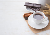 Hot Chocolate in white cups with Chocolate bar on the wooden table
